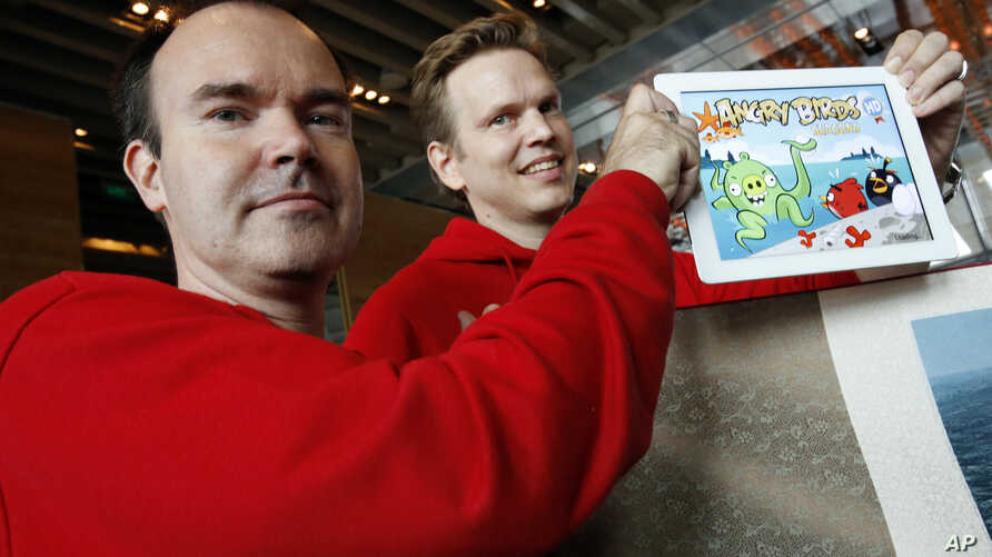 """Peter Vesterbacka, Mighty Eagle, Chief Marketing Officer, left, and Henri Holm, Senior Vice President Of Rovio Asia, right, show the latest version of Angry Birds after the opening ceremony of the Shanghai office of Rovio, maker of popular game """"Angr"""