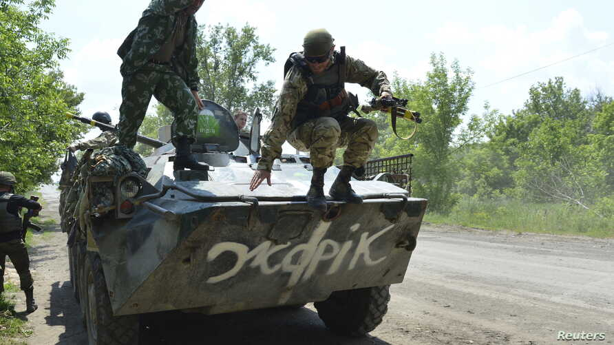 A Ukrainian serviceman jumps from an armoured personnel carrier (APC) in Avdeyevka near Donetsk, Ukraine, June 4, 2015.