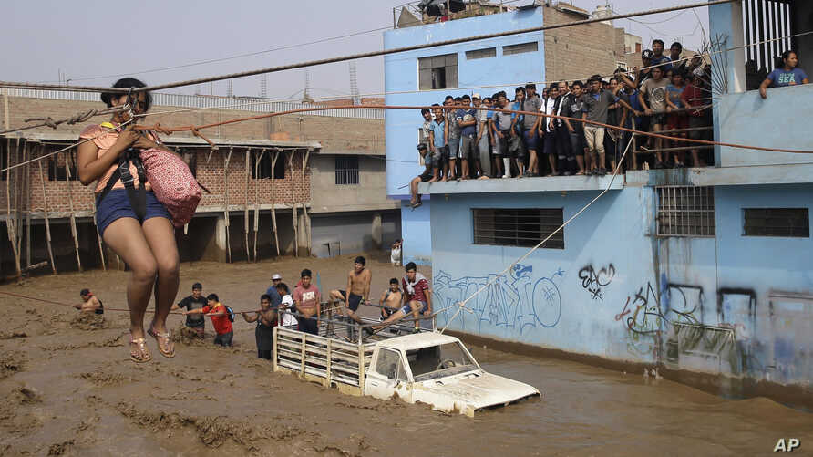 A woman is pulled to safety in a zip line harness in Lima, Peru, March 17, 2017. Intense rains and mudslides over the previous fewe days have wrought havoc around the Andean nation and caught residents in Lima, a desert city of 10 million where it al