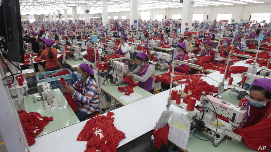 FILE - Garment workers sew clothes in a factory outside Phnom Penh, Cambodia, Aug. 30, 2017.