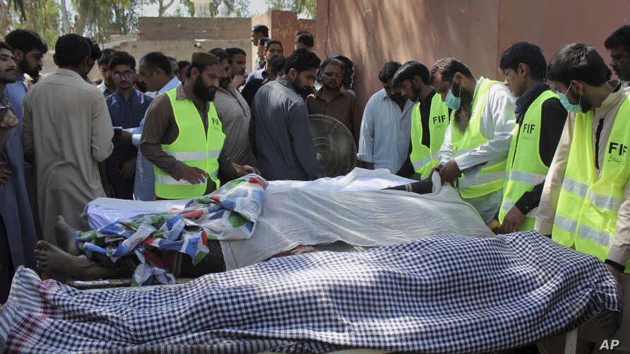 Pakistani volunteers and local residents gather around the bodies of people who were killed in a local shrine, outside the morgue of a hospital in Sarghodha, Pakistan, April 2, 2017.