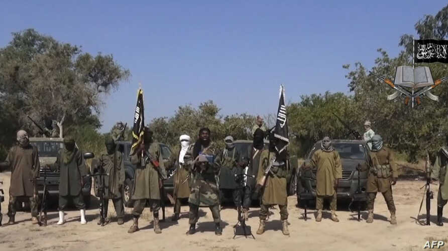 An image grab made on Oct. 31, 2014 from a video obtained by AFP shows the leader of the Islamist extremist group Boko Haram Abubakar Shekau (C) delivering a speech. (AFP photo/Boko Haram)