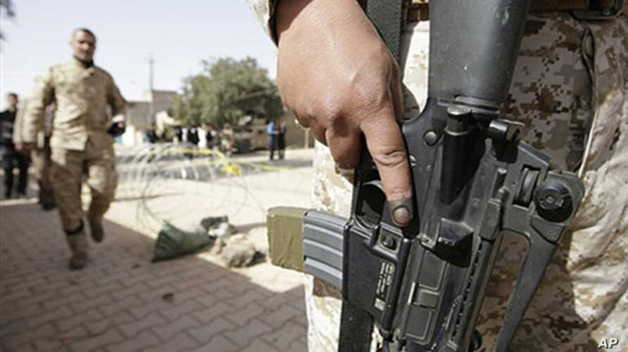An Iraqi army soldier with an ink-stained index finger stands guard at the entrance to a polling station in central Baghdad, 04 Mar 2010