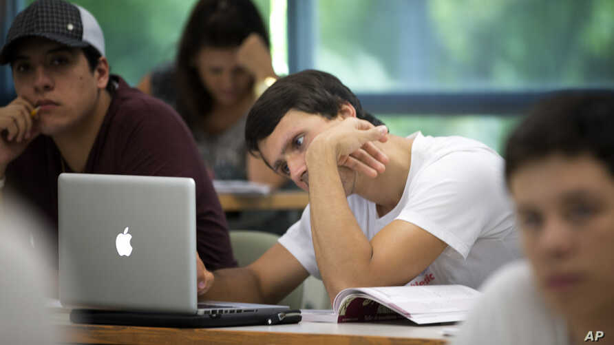 A University of Miami student studies the daily lesson plan on his computer during a Spanish language class in Coral Gables, Florida.