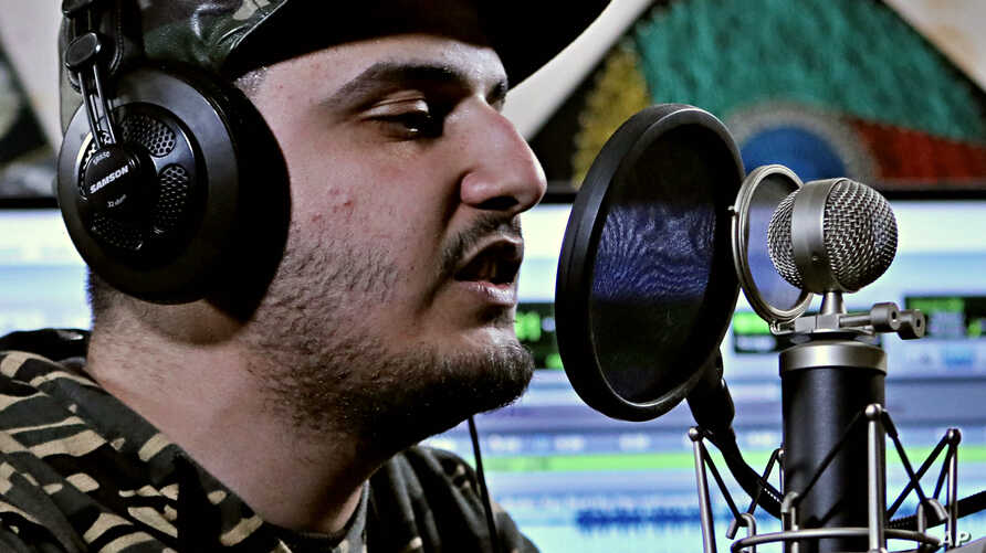 Rapper Ahmed Chayeb records on his computer, Feb. 12, 2019, at his home in the southern port city of Bqasra, Iraq. Chayeb says his generation is fed up with the false piety of politicians and religious authorities who preach about faith and duty but