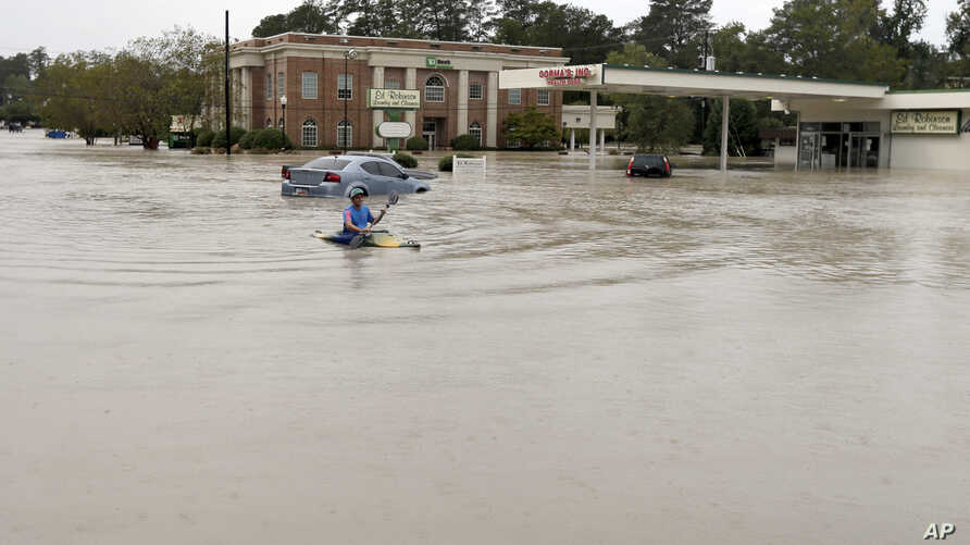 Jordan Bennett, of Rock Hill, S.C., paddles down a flooded a street in Columbia, S.C., Sunday, Oct. 4, 2015.