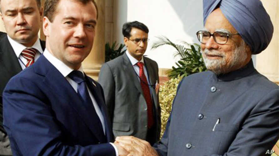 Russian President Dmitry Medvedev, left, and Indian Prime Minister Manmohan Singh shake hands before talks in New Delhi, 21 Dec 2010