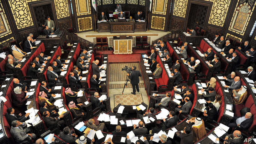 Syrian lawmakers gather during a session to vote for a new election law, at the Syrian parliament in Damascus, Syria, March 11, 2014.