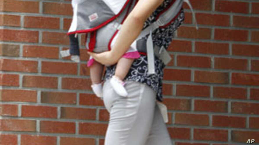A woman who has escaped from North Korea walks into a building as she carries her child at the Hanawon centre, the state-run official temporary base for defectors from the North, in Anseong. The Hanawon was founded July 8, 1999 to help North Korean d