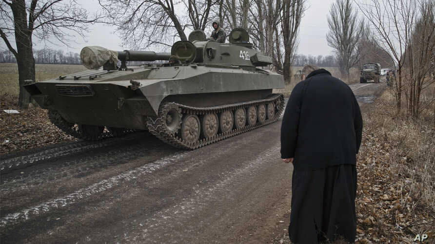 A priest bows as Russia-backed separatist fighters drive in a self propelled 152 mm artillery piece, part of a unit moved away from the front lines, in Yelenovka, near Donetsk, Ukraine,Thursday, Feb. 26, 2015. Russia's foreign minister is sharply cri...