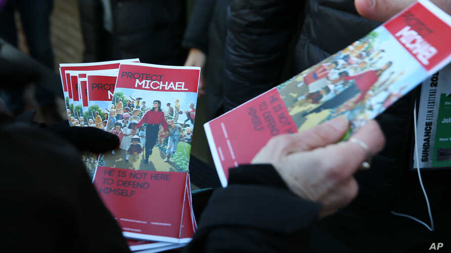 "FILE - Brenda Jenkyns who drove from Calgary, Canada hands out pamphlets in support of Michael Jackson outside of the premiere of the ""Leaving Neverland"" Michael Jackson documentary film at the Egyptian Theatre on Main Street during the 2019 Sundance"