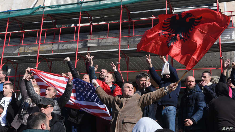 Albanian opposition supporters wave their national flag and a U.S. flag during a protest outside the government building, demanding the resignation of the Albanian prime minister, Feb.16, 2019, in Tirana.