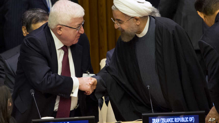 Iraq's President Fuad Masum, left, is greeted by Iranian President Hassan Rouhani as he arrives at the Climate Summit 2014 at U.N. headquarters, Tuesday, Sept. 23, 2014. (AP Photo/Craig Ruttle)