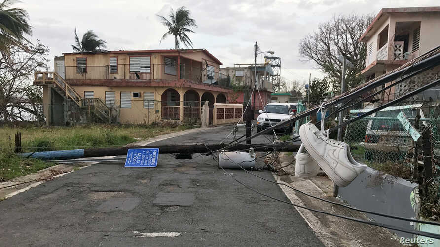Sneakers hang from downed wires in the wake of Hurricane Maria in the Vietnam section of Guaynabo, Puerto Rico, Oct. 1, 2017.