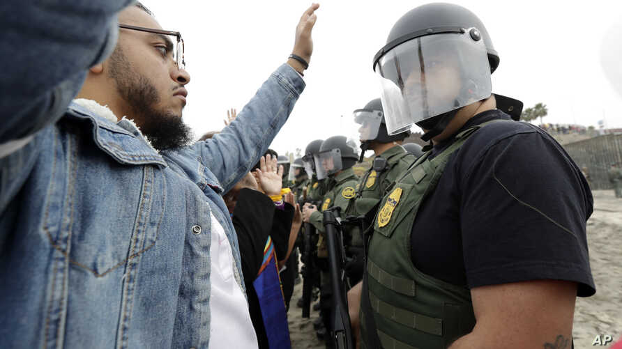 A man holds his hands in the air in front of a line of Border Patrol agents during a protest, Dec. 10, 2018, in San Diego. The protest organized by a Quaker group called for an end to detaining and deporting immigrants and showed support for migrants