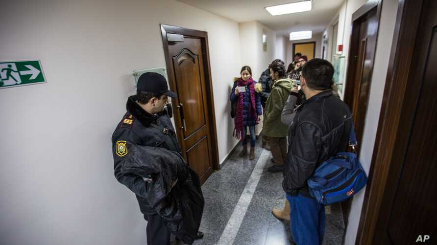 FILE - An Azerbaijani policeman, left, guards as journalists gather at the Radio Free Europe headquarters in Baku, Dec. 26, 2014.