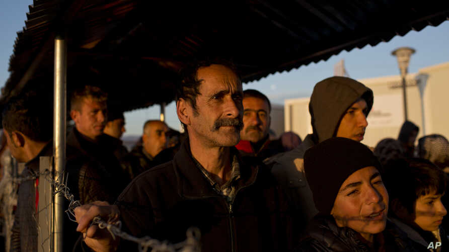Syrian refugees stand in queue to receive food distributed by a non-governmental organization at a refugee camp in the Greek-Macedonian border near the village of Idomeni, Thursday, Feb. 25, 2016.