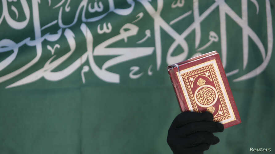 """FILE - A Virginia social studies class learning about Arabic calligraphy was told to write """"There is no god but Allah and Muhammad is the messenger of Allah."""" That message is seen here, from a 2008 banner in Sanaa."""
