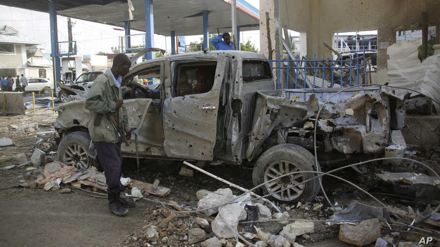 A Somali security man stands looks at the wreckage of a pickup truck near Nasa-Hablod hotel in Mogadishu, Somalia, June 26, 2016.