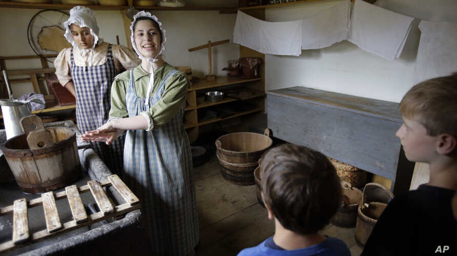 FILE - Hannah Ingersoll (L) and Loralei Arndt (2nd-L) reenact 1830s farm workers as children look on in a cheese room at Old Sturbridge Village, in Sturbridge, Mass., Aug. 22, 2018.