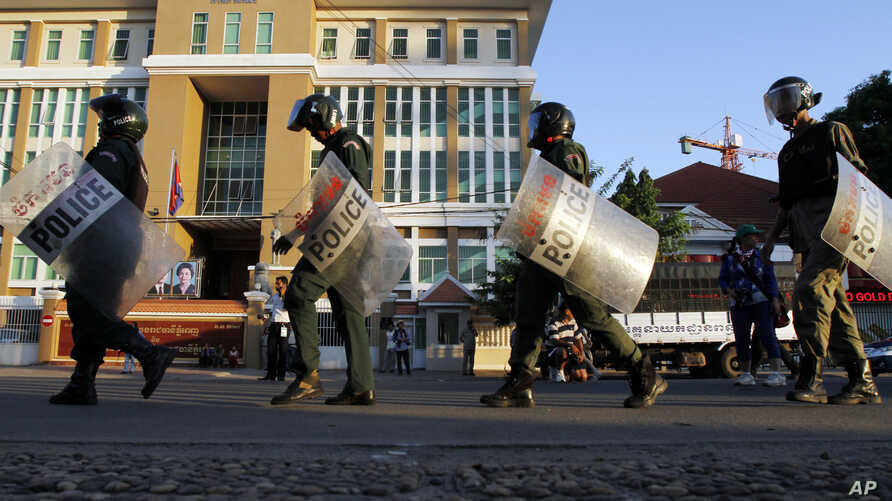 Cambodian riot police officers walk in front of Phnom Penh Municipality Court in Phnom Penh, Cambodia to prepare for providing secutiry Friday, May 30, 2014. The court has convicted almost two dozen factory workers and rights activists for instigatin