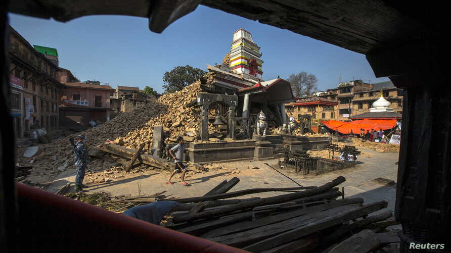 A Nepalese military personnel stands guard inside a compound of Bungamati temple after the earthquake at Bungamati Village, on the outskirts of Kathmandu, Nepal, May 6, 2015.