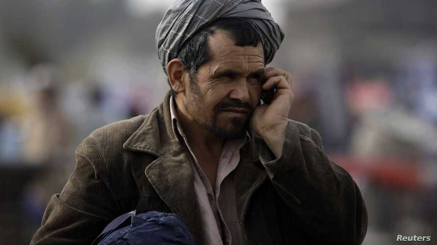 FILE - An Afghan man talks on his mobile phone on a street in Kabul, March 24, 2011. Taliban insurgents recently shut down private telecommunicationcompanies in several parts of the country.