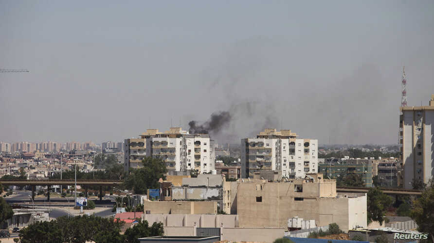 Smoke rises near buildings after heavy fighting between rival militias broke out near the airport in Tripoli July 20, 2014.