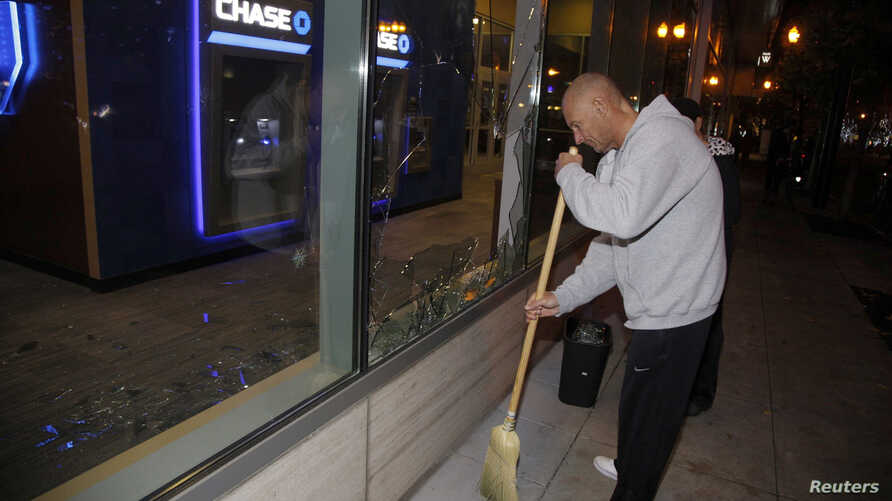 A man sweeps up broken glass after a riot swept through the area in protest to the election of Republican Donald Trump as President of the United States in Portland, Oregon, U.S., Nov. 10, 2016.