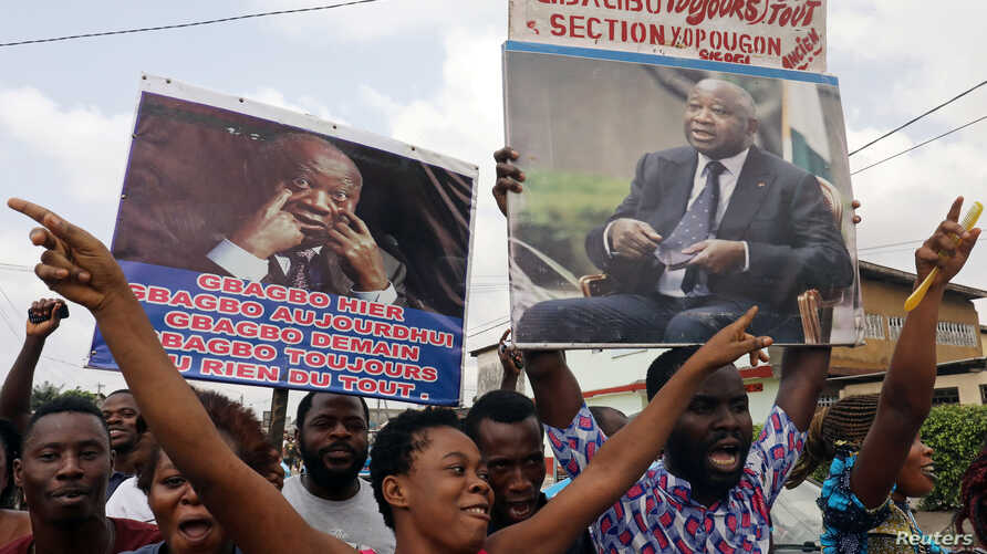 Supporters of former Ivory Coast President Laurent Gbagbo celebrate along a street in Abidjan's Yopougon neighborhood, Ivory Coast Jan. 15, 2019.