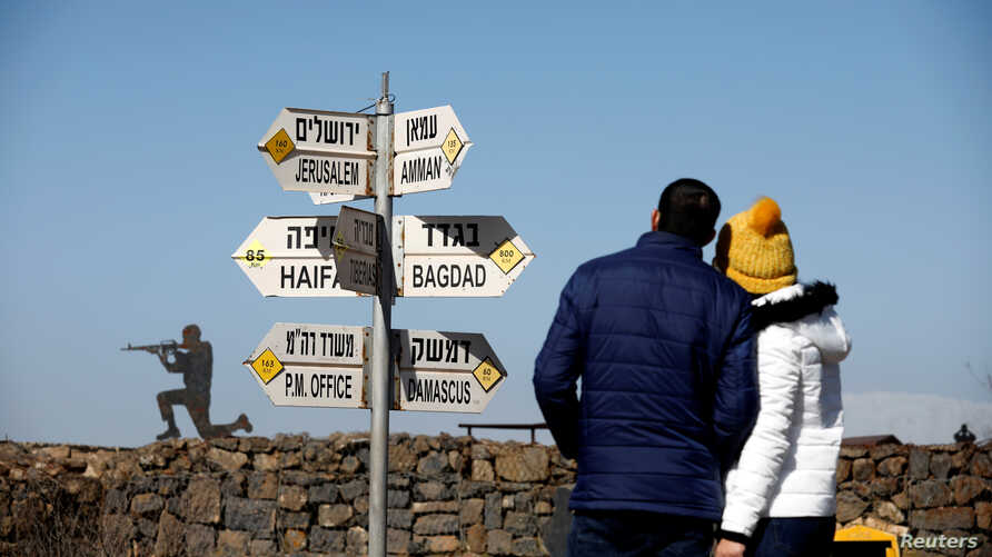 A couple look towards signs pointing out distances to different cities, on Mount Bental, an observation post in the Israeli-occupied Golan Heights that overlooks the Syrian side of the Quneitra crossing, Israel January 21, 2019.