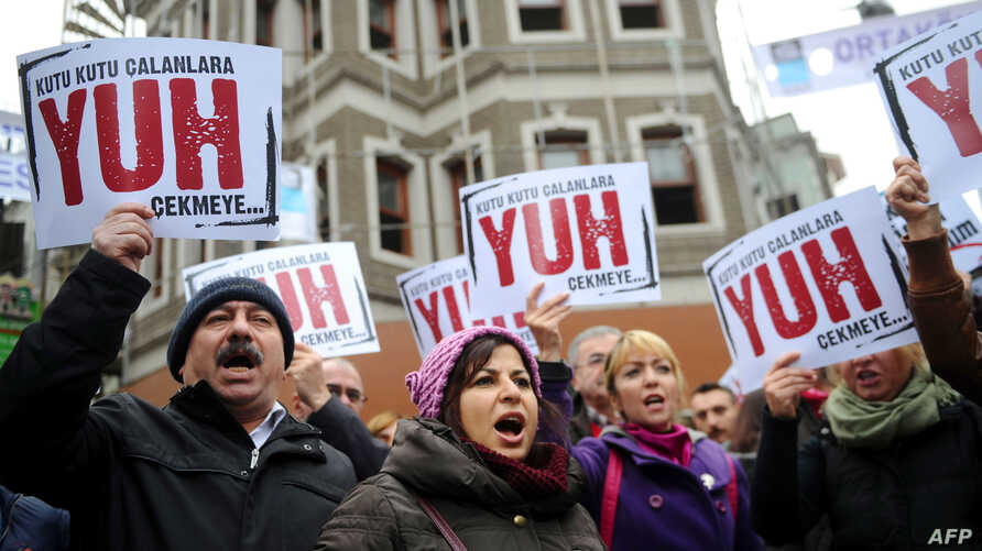 "People hold placards reading ""Shame to thieves with Boxes"" during a demostration on Dec. 29, 2013 in Istanbul against corruption and the Government."