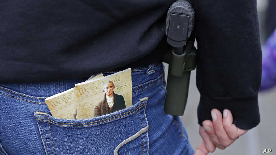 FILE -  a woman wears a gun in a holster next to two copies of the U.S. Constitution during a gun rights rally at the Capitol in Olympia, Wash.