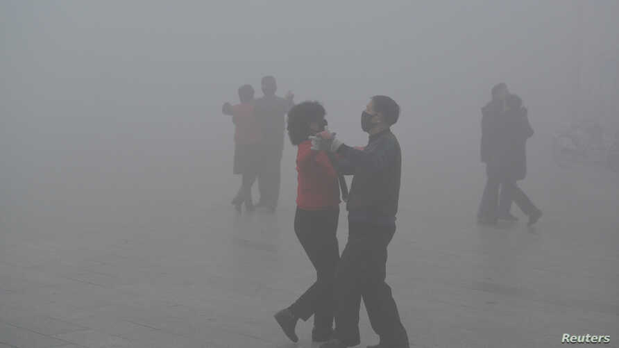 People wearing masks dance at a square amid heavy smog during a polluted day in Fuyang, Anhui province, China, Jan. 3, 2017.