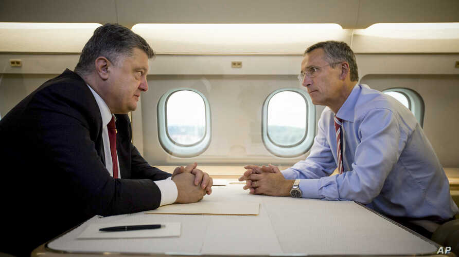 Ukrainian President Petro Poroshenko, left, and NATO Secretary General Jens Stoltenberg talk in a helicopter on the way to a military training ground outside Lviv, western Ukraine, Sept. 21, 2015.