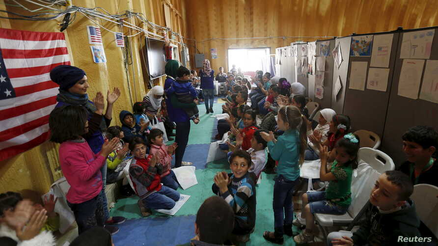 FILE - Syrian refugee children play as they wait with their families to register at the U.S. processing center for Syrian refugees, during a media tour held by the U.S. Embassy in Jordan, in Amman, Jordan, April 6, 2016.