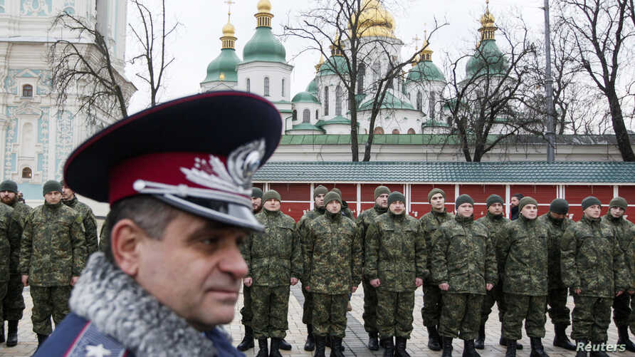 "Members of the newly created Ukrainian interior ministry battalion ""Saint Maria"" take part in a ceremony before heading to military training, in front of St. Sophia Cathedral, in Kiev, February 3, 2015. Members of the battalion will be sent to the fr"