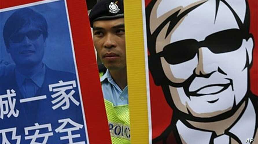 Police officer between images of blind Chinese activist Chen Guangcheng at protest, Hong Kong, May 4, 2012.