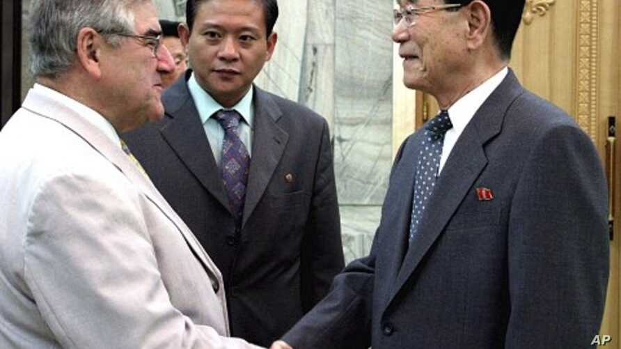 Kim Yong-nam (R), president of the Presidium of the Supreme People's Assembly of N. Korea, shakes hands with Jean-Claude Frecon, who is leading the delegation of the French group, at the Mansudae Assembly Hall in Pyongyang June 3, 2011, in this pictu
