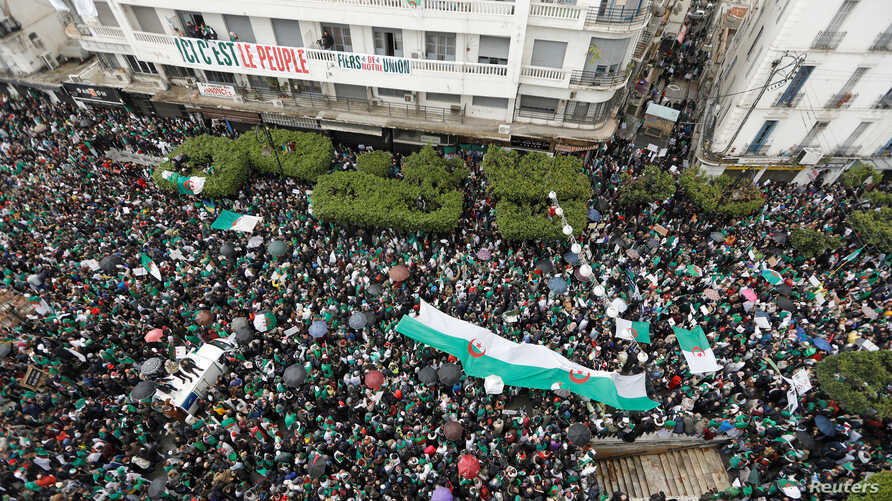 Demonstrators carry Algerian national flags during a protest calling on President Abdelaziz Bouteflika to quit, in Algiers, Algeria, March 22, 2019.
