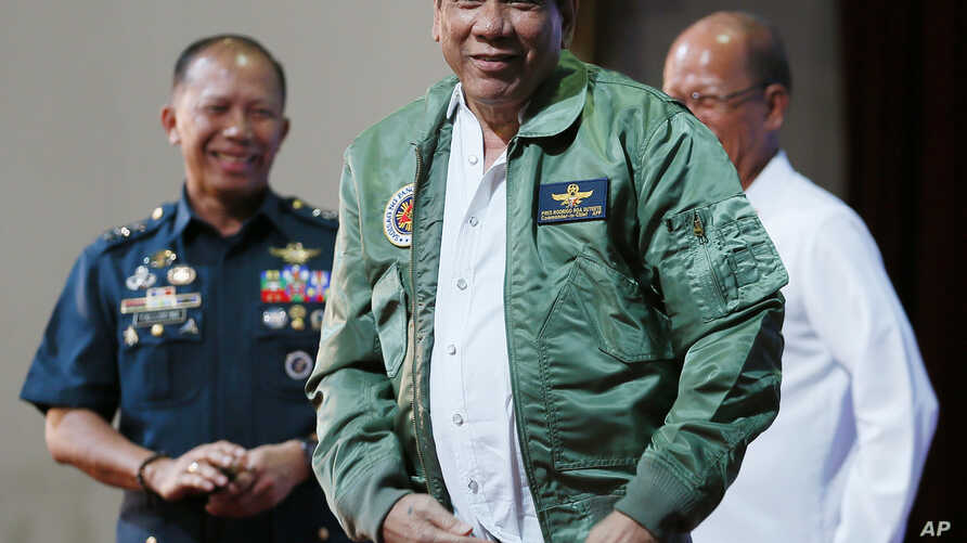 """Philippine President Rodrigo Duterte, center, smiles as he is presented with a pilot's jacket during his """"Talk with the Airmen"""" on the anniversary of the 250th Presidential Airlift Wing Tuesday, Sept. 13, 2016 at the Philippine Air Force headquarters"""