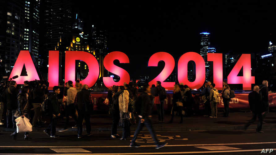 People gather next to a sign reading AIDS 2014 in Melbourne on July 18, 2014 after news that downed Malaysia Airlines flight MH17 was carrying many participants headed to the 20th International AIDS Conference planned this weekend in the Australian c