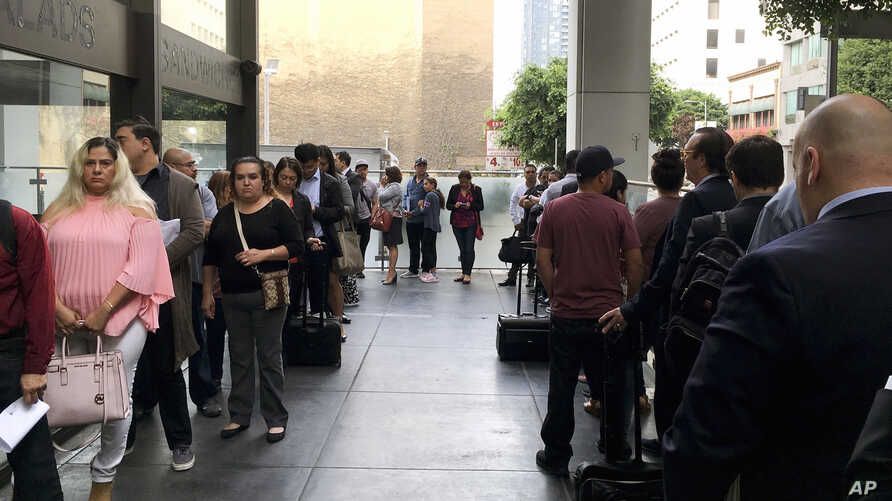 FILE - Immigrants awaiting deportation hearings line up outside the building that houses the immigration courts in Los Angeles, June 19, 2018.