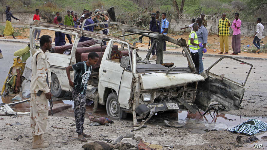 A Somali soldier, left, stands by the wreckage of a minibus that was destroyed in a suicide car bomb attack near the defense ministry compound in Mogadishu, Somalia, April 9, 2017.