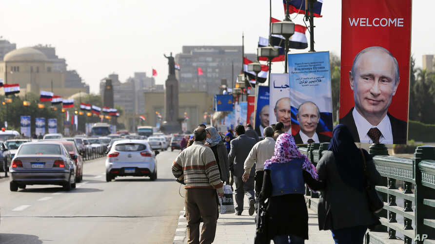 Posters of Russian President Vladimir Putin hang on light poles on Qasr El Nile Bridge in Cairo, Egypt, Monday, Feb. 9, 2015. Putin will visit Egypt for two days.