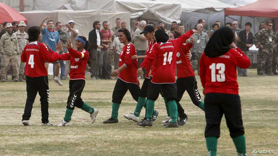 FILE - The Afghan national women's soccer team celebrates a victory in a friendly match against a women's team from the NATO-led International Security Assistance Force in Kabul, Oct. 29, 2010.