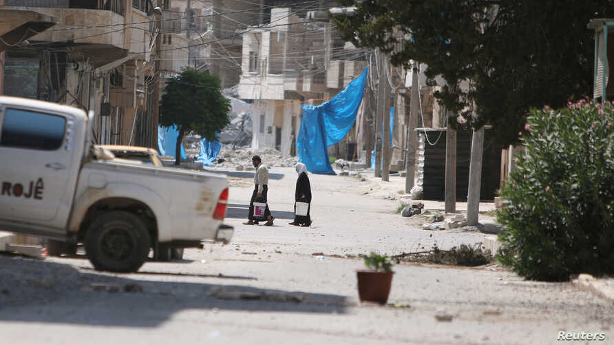 Residents carry buckets as they cross a damaged street near blue sheets used as a cover from snipers in Manbij, in Aleppo governorate, Syria, Aug. 7, 2016.