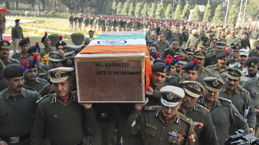 Indian Border Security Force officers carry the coffin of a colleague killed Wednesday in an India-Pakistan cross-border firing, in Jammu, India, Jan. 1, 2015.