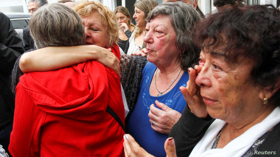 Relatives of former workers at Ford Motor Co. local plant and ex-political prisoners react after two former Ford executives were convicted during the trail, in Buenos Aires, Argentina, Dec. 11, 2018.
