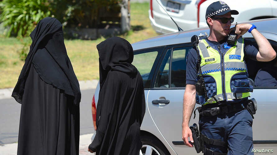 Two women stand next to a policeman blocking a road where police officers are searching a house in the Melbourne suburb of Meadow Heights, Australia, Dec. 23, 2016.